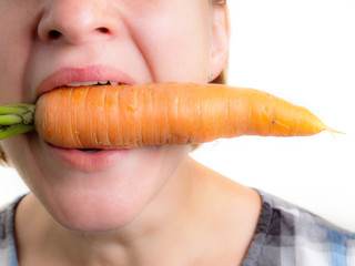Woman with fresh carrot in her mouth