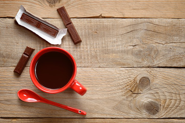 Coffee cup with chocolate on wooden background