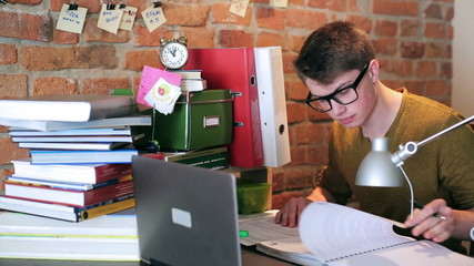 Young student doing assignment and studying at home