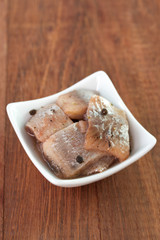 herring in white dish on brown background