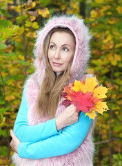 beautiful woman in autumn park with an armful of maple leaves