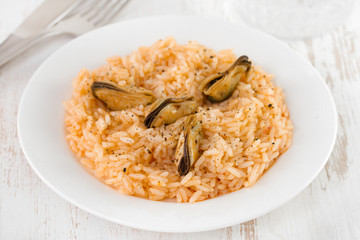 rice with mussels on plate and glass of water