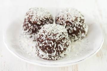 chocolate coconut sweets on plate on white background