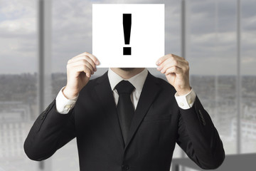 businessman hiding face exclamation mark