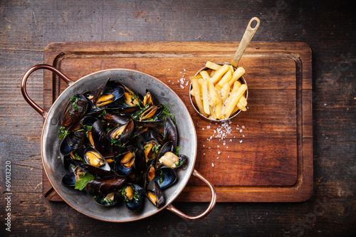 Fotobehang Schaaldieren Mussels in copper cooking dish and french fries on dark wooden b
