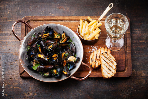 Mussels in copper cooking dish and french fries on dark wooden b - 69013288