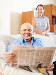 Happy mature couple reading newspaper  together