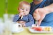 Baby boy having piece of bread