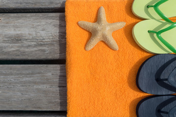 Beach slippers, towel and starfish on wood background.