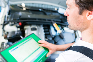 KFZ-Mechaniker mit Diagnosegerät in Autowerkstatt