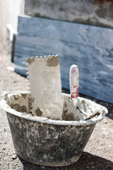 A bucket full of tools to renovation an external wall