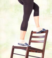 Unfallgefahr im Haushalt - Frau steigt auf eine Stuhllehne