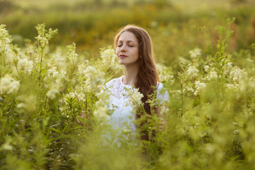 Happy woman with eyes closed among the wildflowers