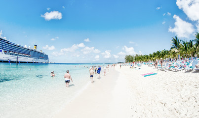 Beach with turquoise waters and cruise ship on a beautiful day