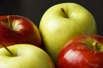 Four apples on black background.