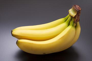 Ripe yellow bananas on dark background