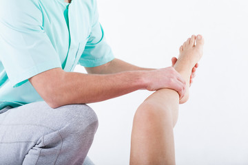 Physiotherapist bending knee