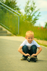Skater boy child with his skateboard. Outdoor activity.
