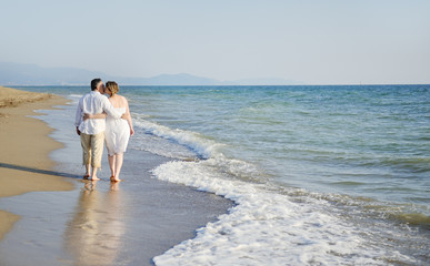romantic couple walking together on the beach