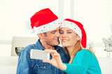 Happy couple in their 30s making a selfie for Christmas at home poster