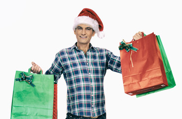Smiling man with Christmas hat carrying colourful bags. Isolated