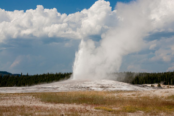 Old Faithful Eruption Against White Clouds