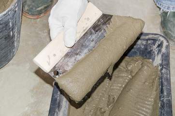 Tiler taking tile adhesive with a notched trowel