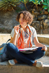 Young beautiful woman with curly hair thinking and writing in ex