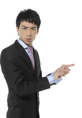 Young business man in suit pointing at copy space