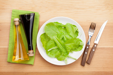 Plate with fresh salad, condiments, knife and fork. Diet food