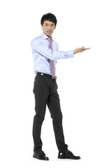 Full body young business man in suit pointing at copy space