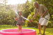 Grandparent and grandkid playing with hose
