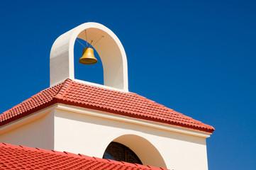 Dach einer Kirche mit goldener Glocke