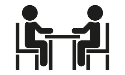 Zwei Menschen sitzen am Tisch