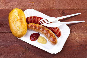 Roasted sausage with bread served on a paper tray