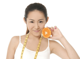 young fit woman with slice orange fruit and a tape measure