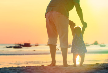 father and little daughter walking on sunset beach
