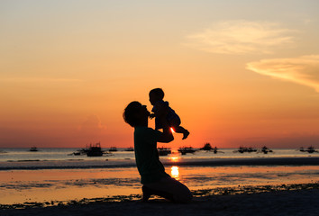 Father and little daughter silhouettes on sunset beach