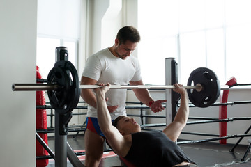 Coach insures athlete exercising with barbell