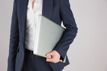 Businesswoman in suit holding laptop