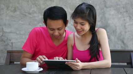 lovely young couple using and typing digital tablet computer