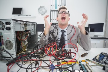 Stressed computer engineer working on broken cables