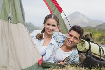 Happy couple in tent on countryside landscape