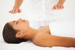 Beautiful brunette getting reiki therapy