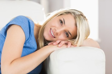 Portrait of a smiling young woman sitting on sofa