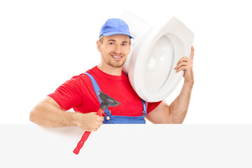 Male plumber holding a toilet bowl behind a panel