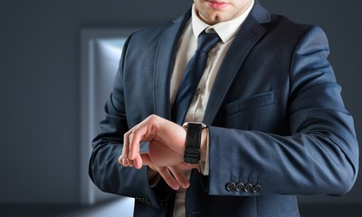 Composite image of businessman checking the time on watch
