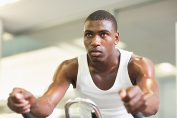 Determined man working out on exercise bike at gym