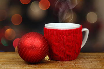 Christmas ball and hot drink in a cup in front of sparkle lights