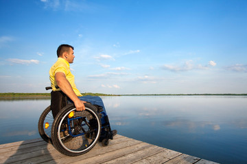 Rollstuhlfahrer schaut auf den See